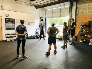 Bootcamp coach demonstrating medball slams to a group in a gym